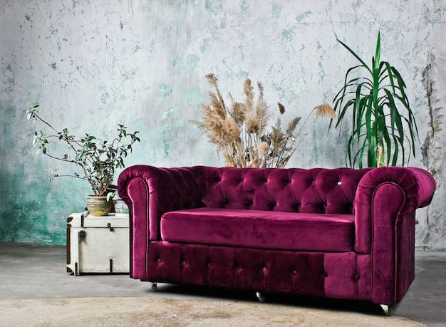 Sofá roxo vintage contra uma parede rústica. interior rústico