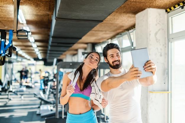 Sofá tomando auto-retrato com tablet enquanto mulher desportiva com toalha em volta do pescoço posa. interior do ginásio.