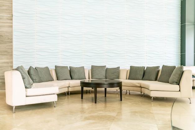 Sofá vazio com travesseiro no lobby do hotel