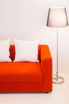 Sofá vermelho com travesseiro e lâmpada de luz