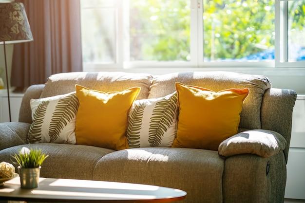 Sofá vintage e almofadas na sala de estar com luz do sol da manhã