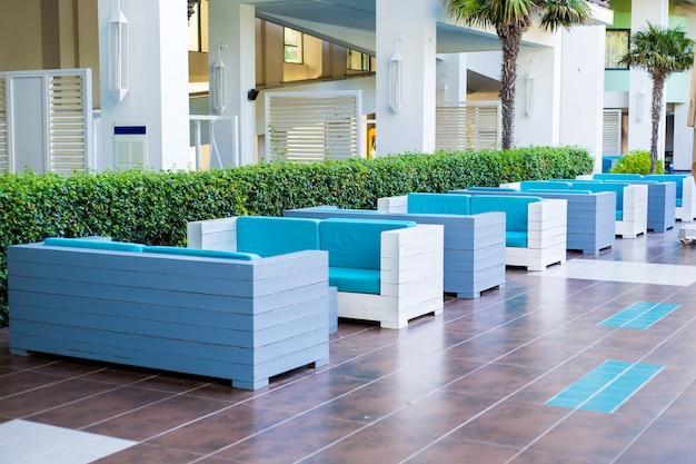 Sofás azuis em uma fileira ao ar livre no hotel lobby, parede de espaços verdes