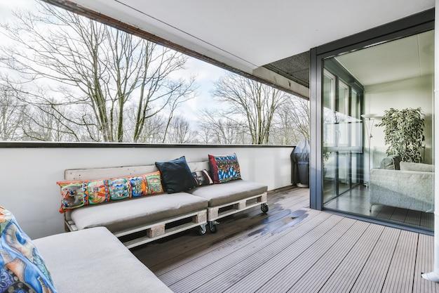 Sofás confortáveis com almofadas ornamentais localizados na varanda molhada perto das paredes de vidro de um apartamento moderno