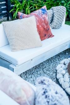 Sofás e bancos com almofadas ao redor da lareira na horta