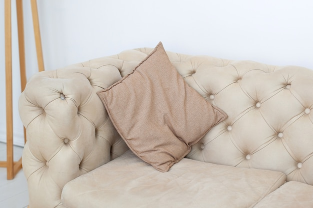 Sofás interiores texturizados e tons neutros. almofada no sofá na sala. almofada marrom em um sofá elegante na sala de estar. decoração, detalhes interiores. casa de estilo escandinavo. design do quarto
