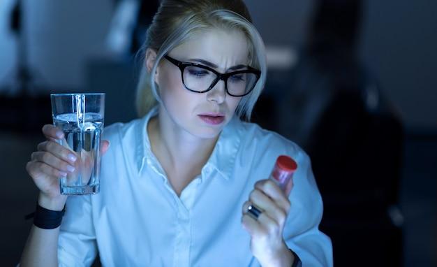 Sofrendo com a dor. mulher de negócios muito cansada e exausta sentada no escritório segurando comprimidos enquanto sofre de dor