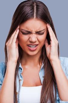 Sofrendo de dor de cabeça. mulher jovem e bonita sofrendo de dor de cabeça em pé contra um fundo cinza
