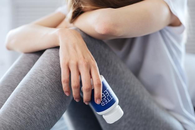 Sofrendo de insônia. mulher jovem e magra sentada segurando comprimidos para dormir