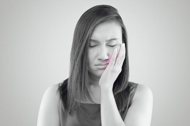 Sofrendo de uma dor de dente, mulher asiática vestindo uma camisa vermelha, sofrendo
