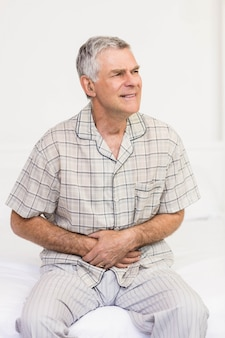 Sofrendo sênior homem segurando sua barriga em casa