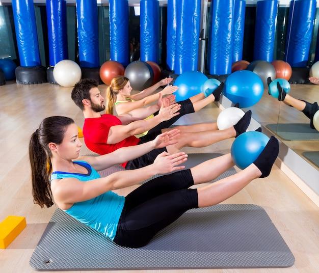 Softball de pilates o grupo teaser exercício no ginásio