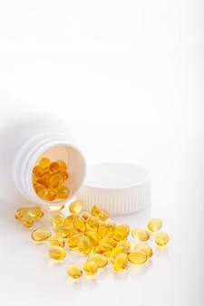 Softgel de óleo de peixe de ouro espalhado da garrafa no fundo branco