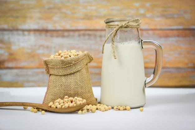 Soja e grãos de soja secos na tigela branca - leite de soja em frasco de vidro para uma dieta saudável e proteína natural do feijão