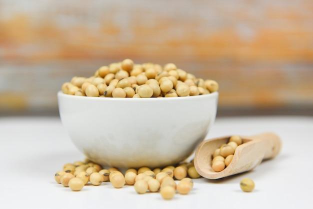 Soja em bolw e madeira fundo - grãos de soja seca