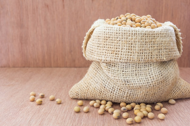 Soja em saco de saco de cânhamo com leite de soja em configuração de vidro na mesa de madeira