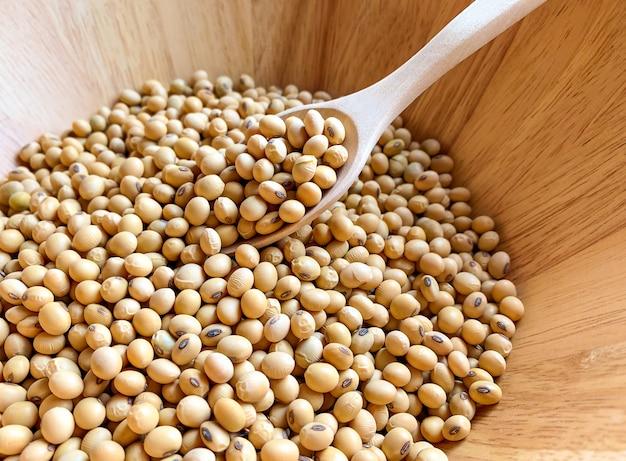 Soja em uma tigela de madeira e colher de pau para colher sementes de soja