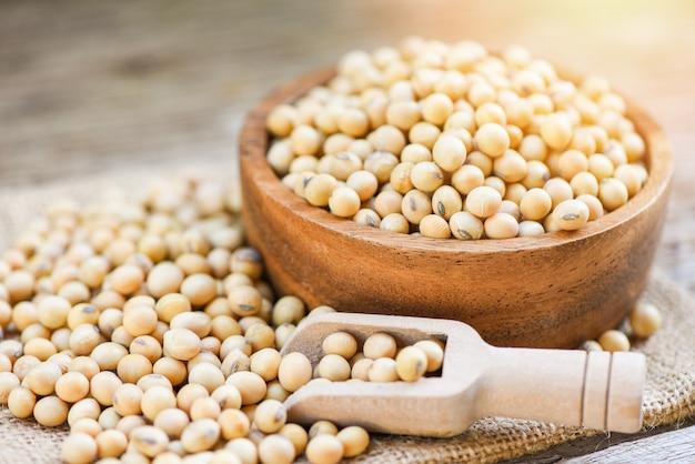 Soja em uma tigela de madeira produtos agrícolas no saco - grãos de soja seca