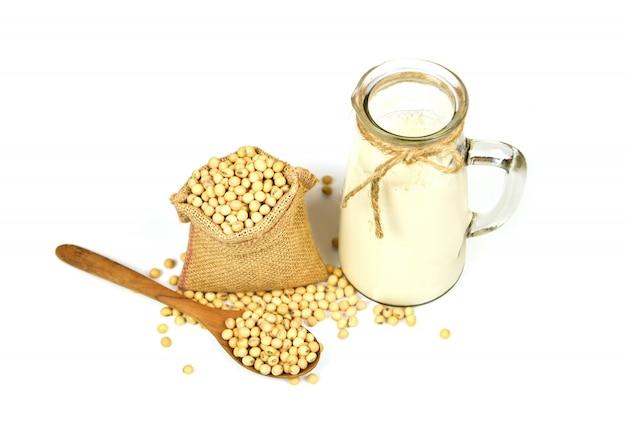 Soja na colher de pau e grãos de soja secos no saco isolado no fundo branco