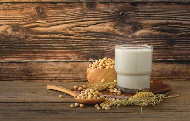 Soja saudável no chão de madeira, xícara de madeira, colher de pau juntos como um grupo, espaço de cópia