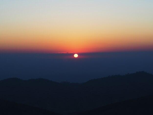 Sol ao nascer do sol com a montanha embaçada e céu