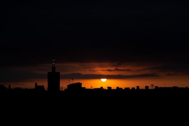 Sol aparece por trás das nuvens, vista superior do telhado de uma antiga torre da igreja.