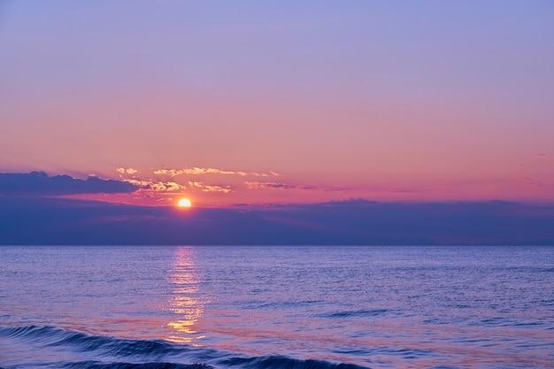 Sol atrás de uma enorme nuvem sobre a água ondulante na costa marítima tropical