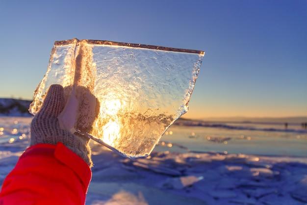 Sol brilha através de um pedaço de gelo claro em uma mão