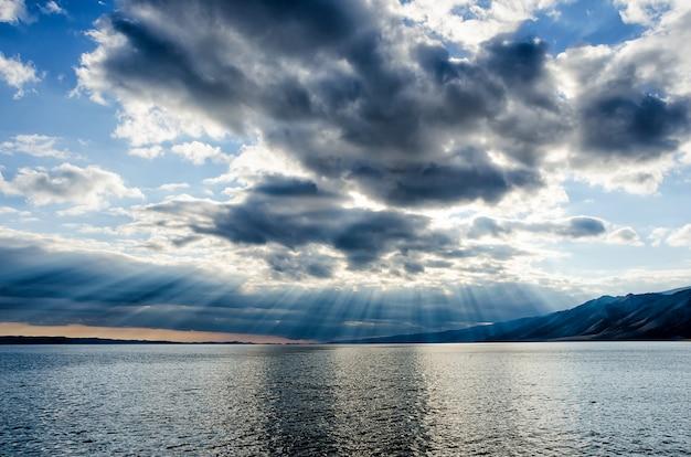 Sol brilhando no céu nublado e espesso, forro de prata