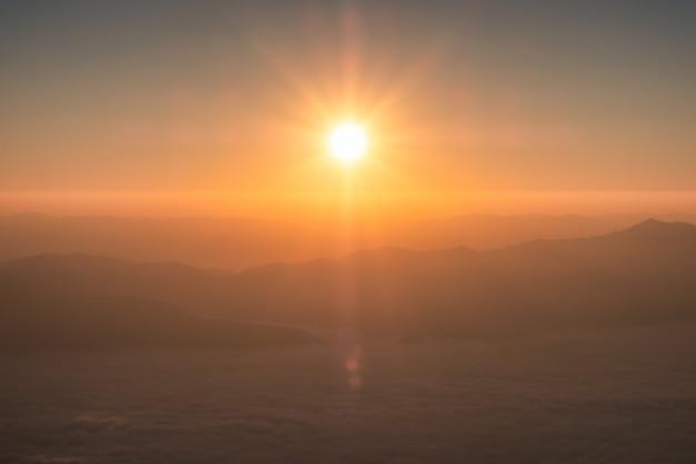 Sol brilhando sobre o horizonte com a montanha