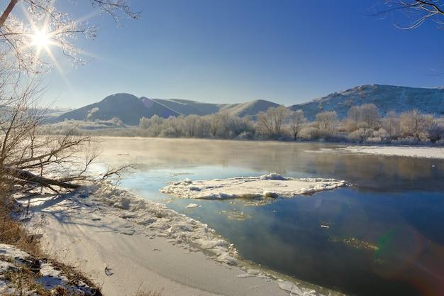 Sol brilhante no céu sem nuvens. rio congelando das margens montanhosas e grandes blocos de gelo.