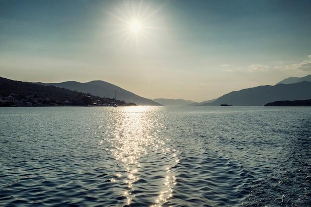 Sol brilhante sobre o mar com vista para as montanhas. mar adriático no montenegro. turismo e viagens. espaço para texto.