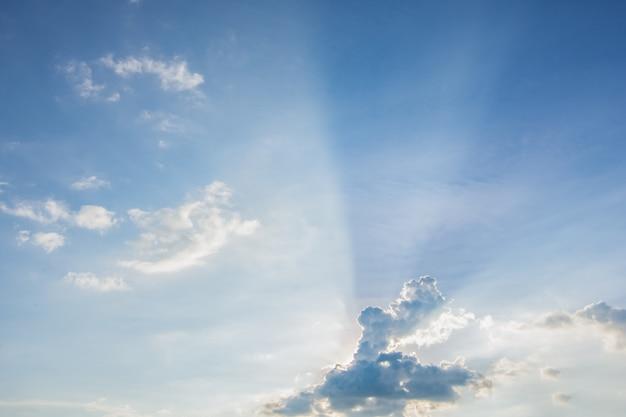 Sol, céu azul e nuvens.