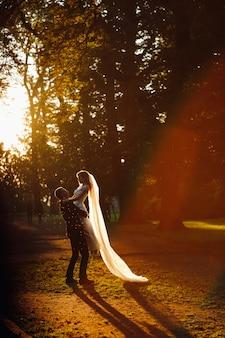 Sol de verão à noite faz uma auréola em torno do lindo casal de noivos