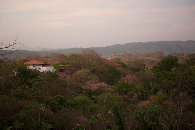 Sol enfraquecendo sobre uma casa branca com um telhado laranja nas colinas acima das copas das árvores da costa rica