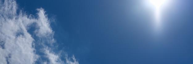 Sol forte brilhando no céu azul com nuvens de fundo
