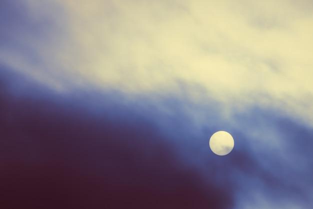 Sol frio brilha através da névoa espessa no fundo do tempo nublado