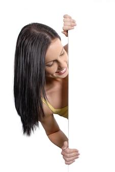 Sol menina bronzeada espreitar em volta de um quadro branco