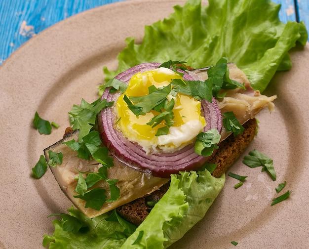 Sol over gudhjem - prato dinamarquês, um sanduíche aberto com rugbrod, arenque defumado, cebolinha e gema de ovo crua, cozinha dinamarquesa