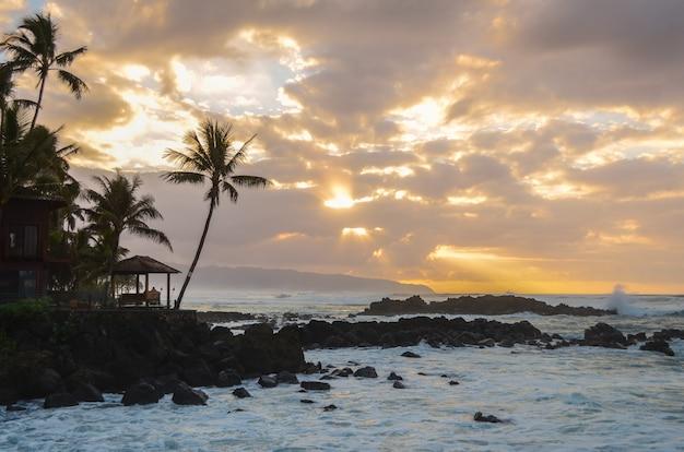 Sol rompendo as nuvens como ondas espirrar nas rochas no uppers beach park em oahu, haw
