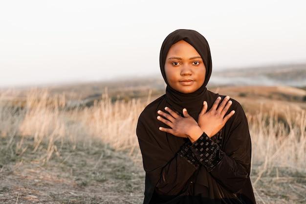 Solat tradicional orando a deus no tapete. mulher muçulmana negra orando a alá. tradição nacional do ramadã.