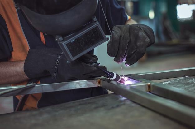 Solda de argônio, trabalhadores mascarados e luvas de couro para segurança, soldagem de argônio em p industrial