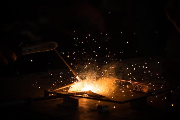Solda, metal trabalhando em fundo escuro