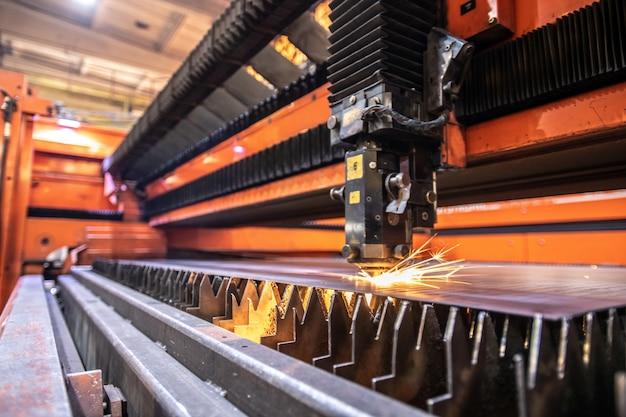 Solda ou corte de chapa de ferro de processamento de máquina industrial em substrato serrilhado em instalações industriais modernas
