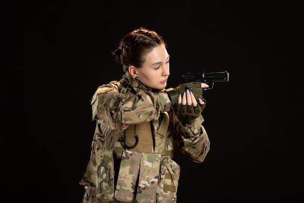 Soldada camuflada apontando a arma na parede preta