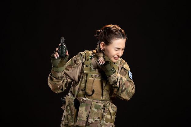 Soldada camuflada com uma granada nas mãos na parede preta