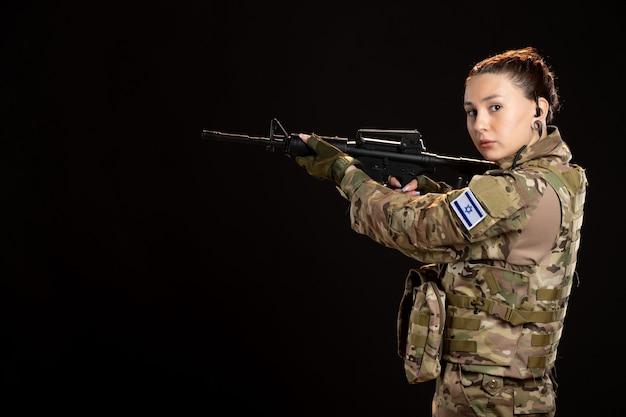 Soldada camuflada mirando metralhadora na parede escura