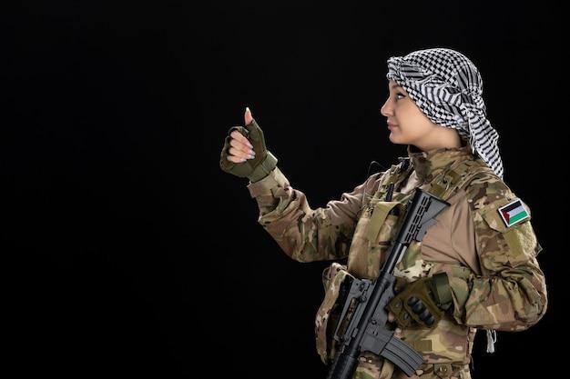 Soldada em uniforme militar com rifle na parede preta