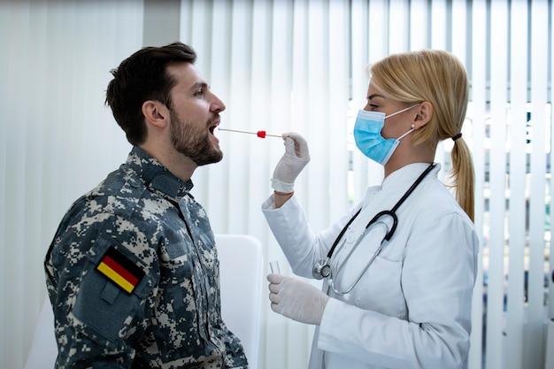 Soldado alemão uniformizado fazendo teste pcr no consultório médico durante a epidemia do vírus covid19