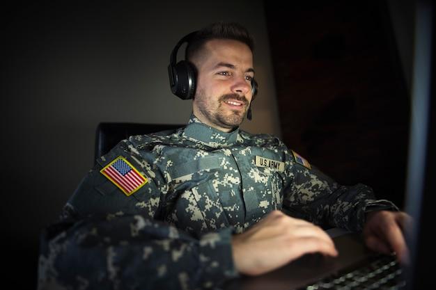 Soldado americano com fone de ouvido na frente do laptop trabalhando no centro de inteligência