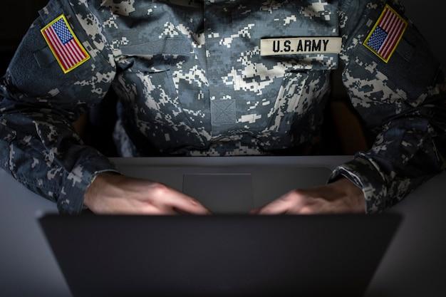 Soldado americano irreconhecível em uniforme militar usando computador na comunicação - centro de inteligência para vigilância e proteção de fronteira